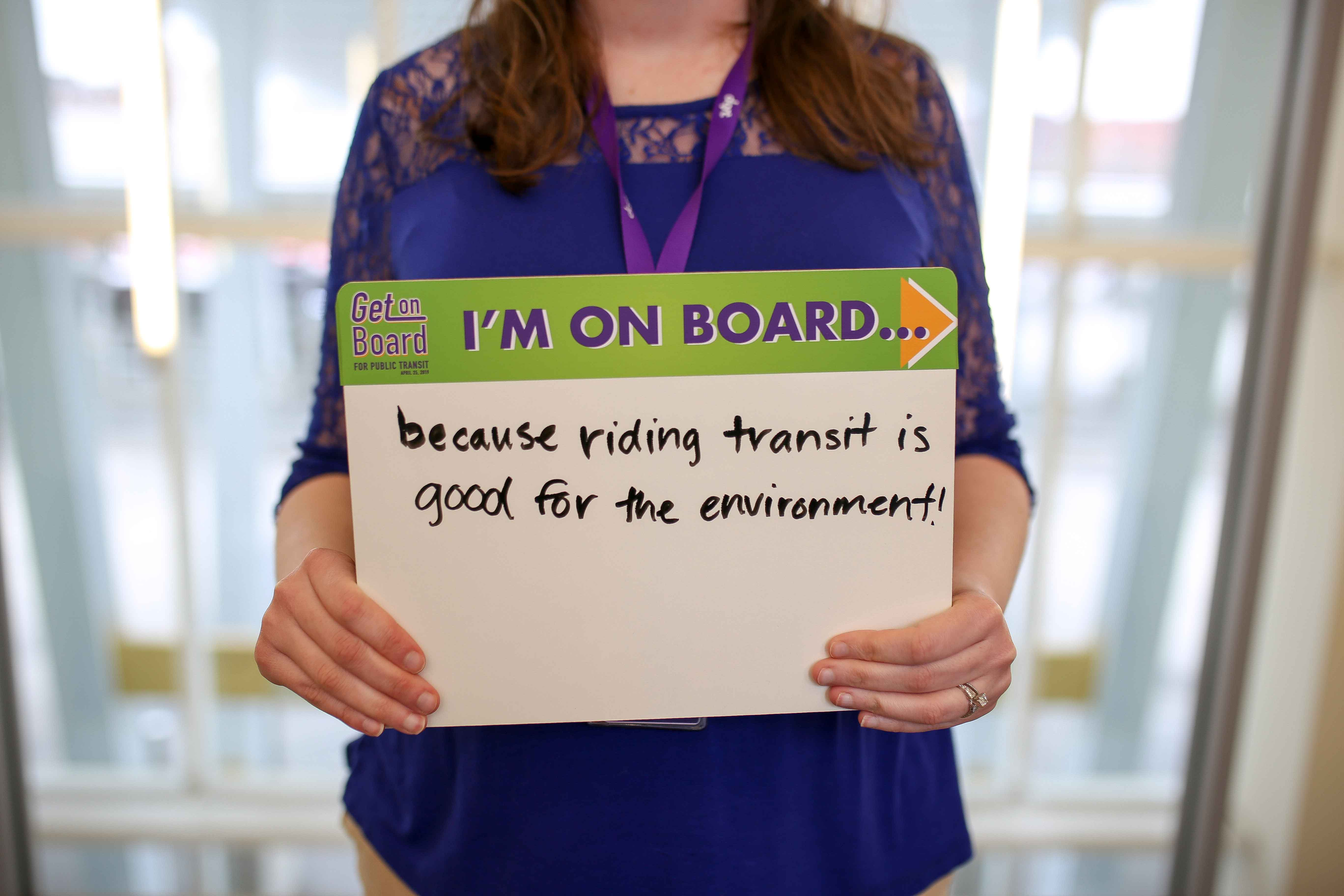 "Woman in blue shirt poses with sign reading ""I'm on board because riding transit is good for the environment."""